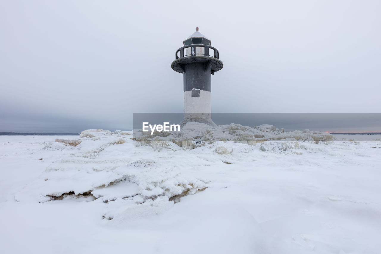 guidance, lighthouse, tower, security, safety, built structure, architecture, protection, cold temperature, building, water, nature, direction, building exterior, no people, sea, white color, winter, outdoors, horizon over water