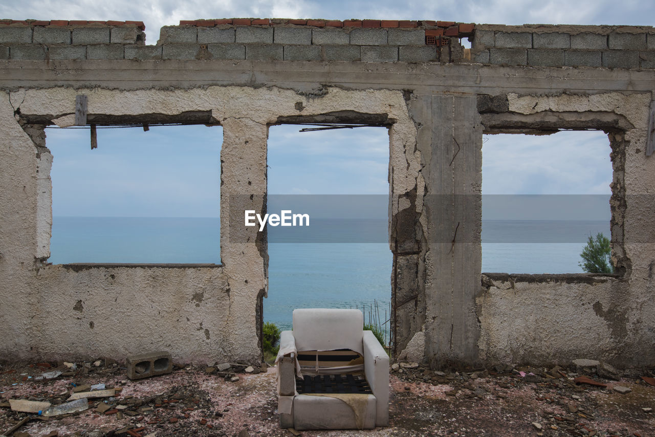 VIEW OF ABANDONED BUILDING BY SEA