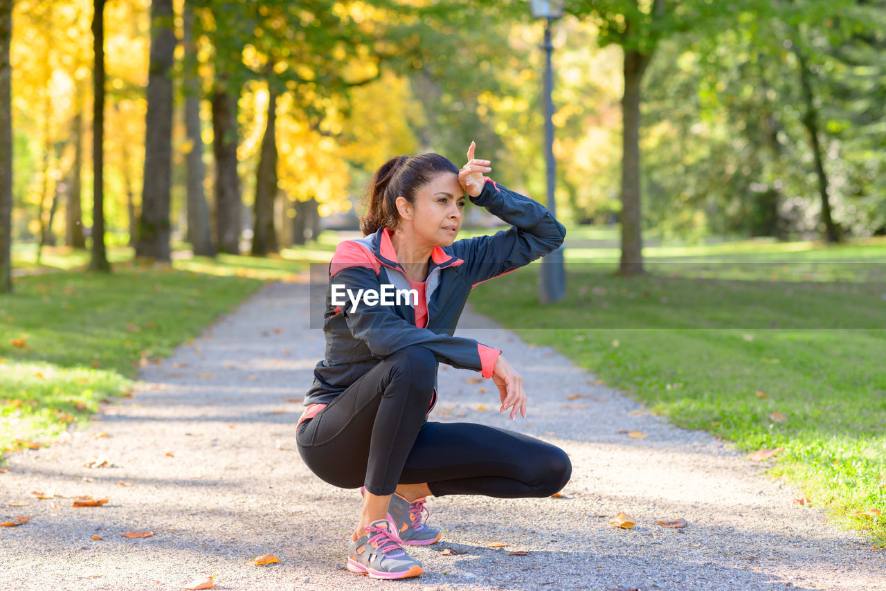 Tired mature woman crouching on footpath at park