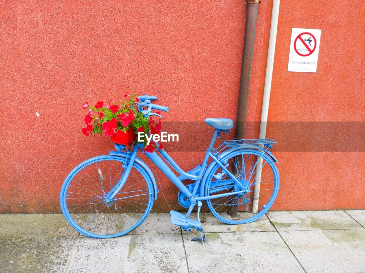 Bicycle parked against red wall