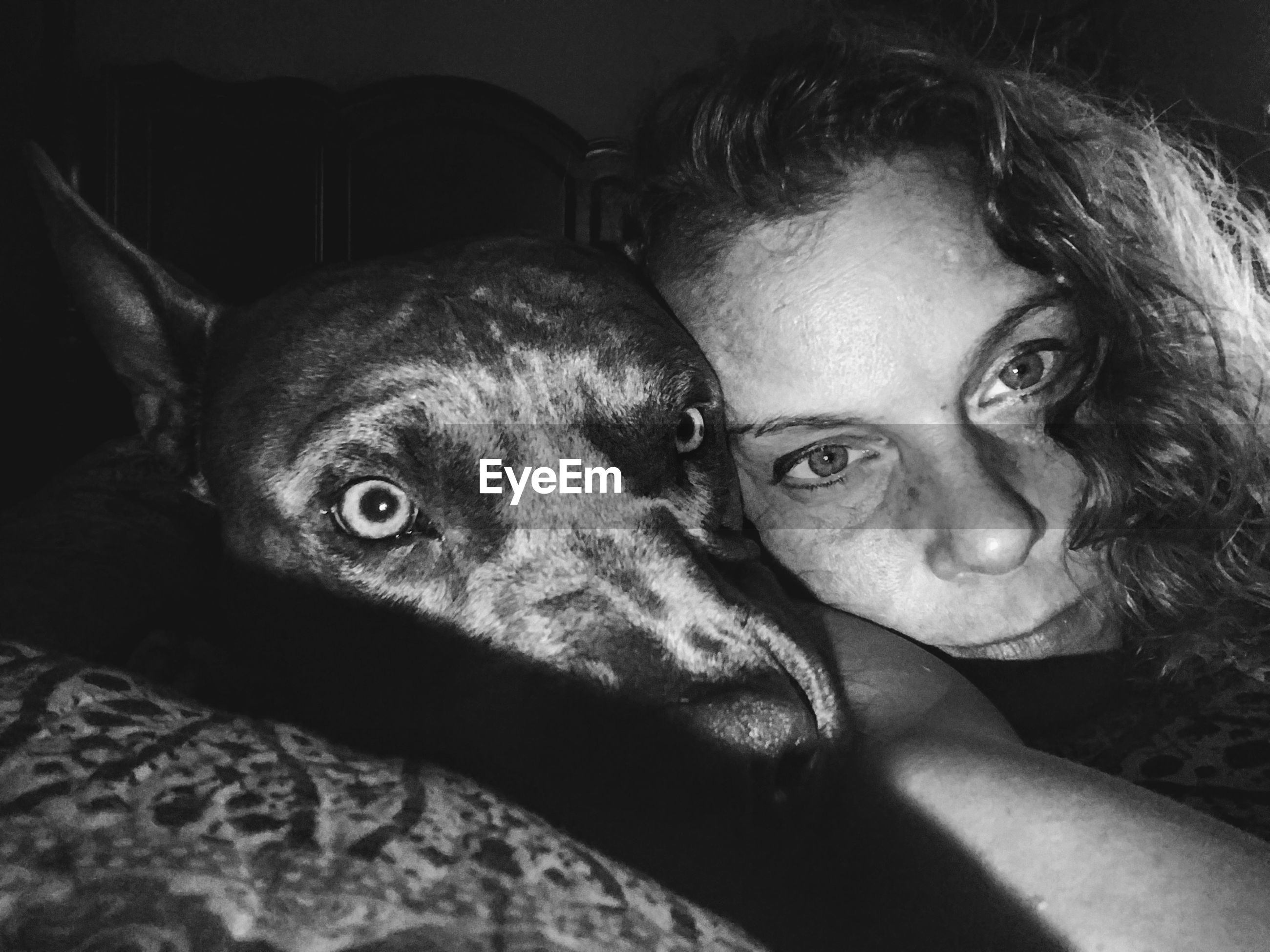 Portrait of woman with dog in darkroom