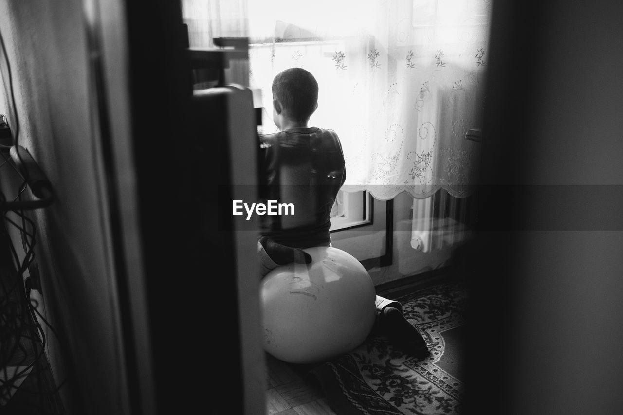 window, indoors, looking through window, curtain, one person, rear view, real people, home interior, standing, day, people