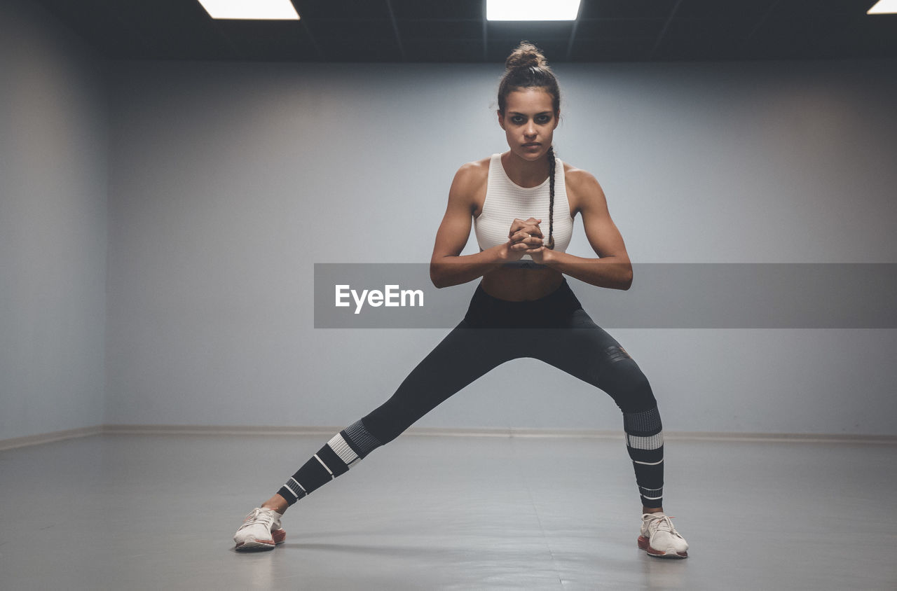 full length, one person, indoors, front view, exercising, lifestyles, portrait, young adult, looking at camera, healthy lifestyle, sport, practicing, young women, dancing, women, sports clothing, leisure activity, confidence, skill