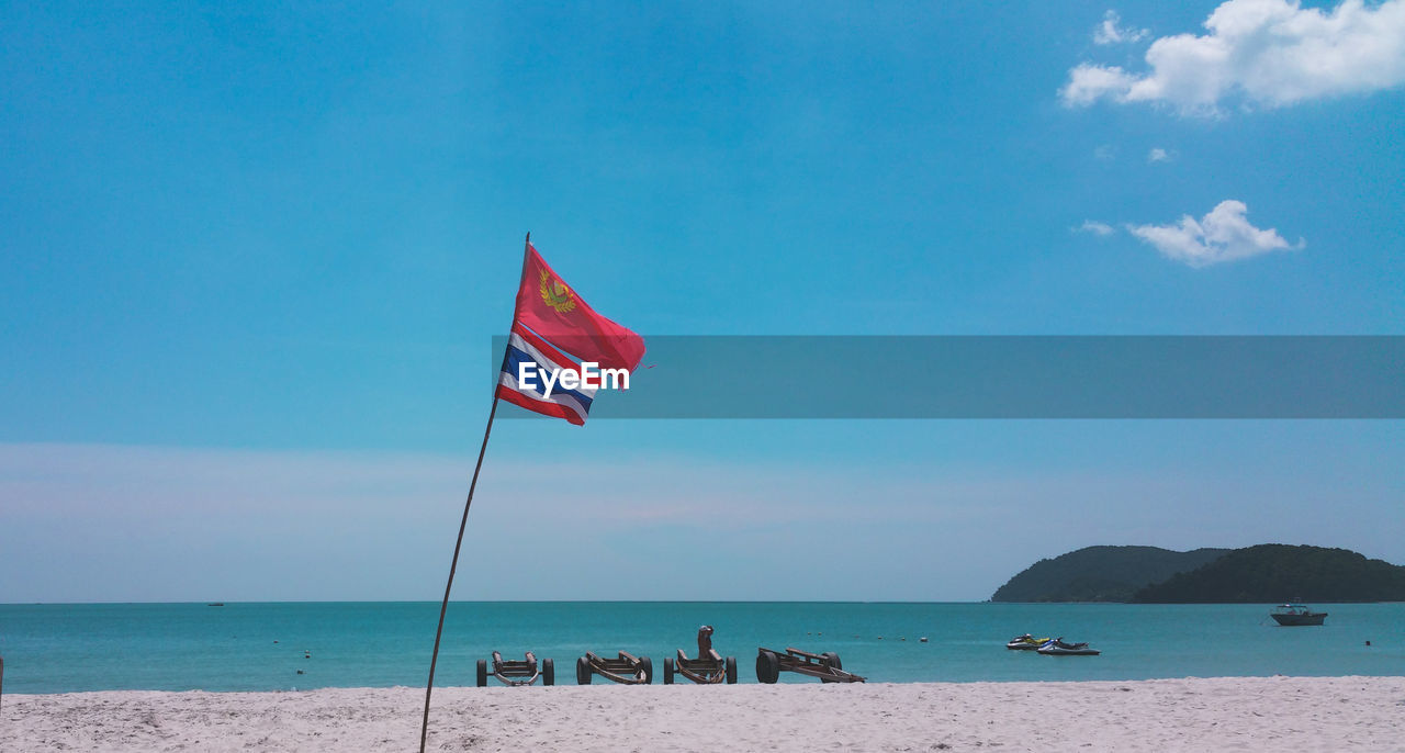 water, sky, sea, land, nature, beach, flag, scenics - nature, blue, day, horizon, patriotism, horizon over water, cloud - sky, beauty in nature, tranquility, tranquil scene, incidental people, wind, outdoors