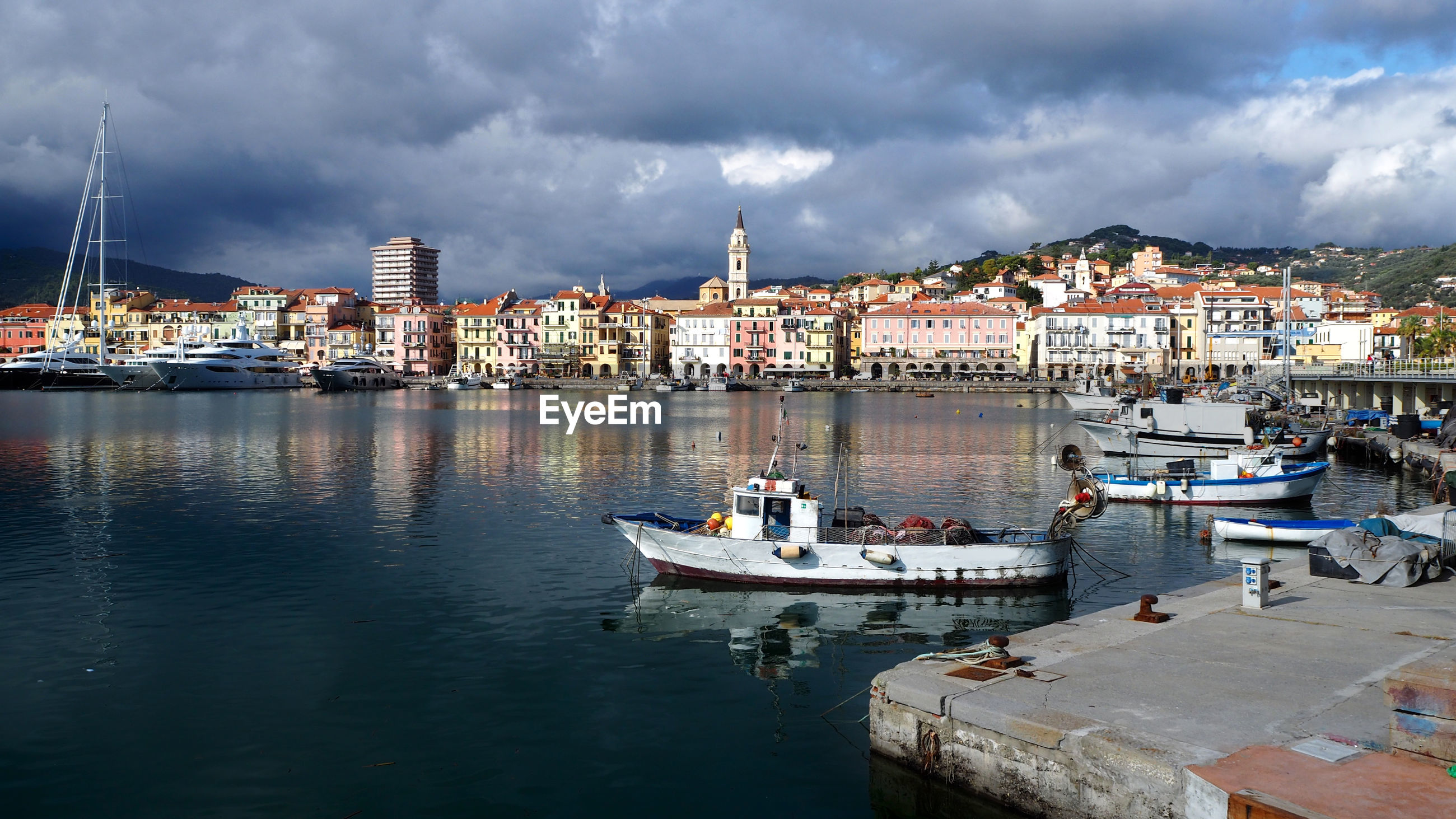 BOATS IN HARBOR BY BUILDINGS AGAINST SKY