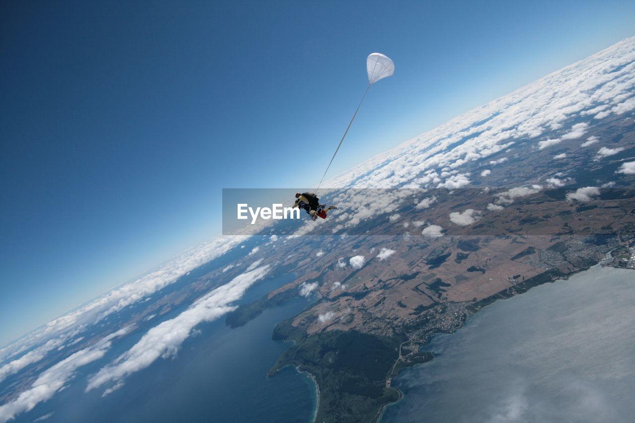 Man Paragliding Against Clear Blue Sky