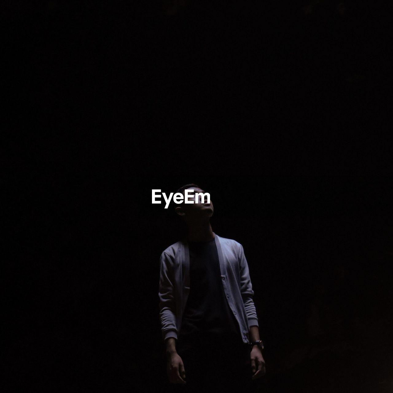 Full length of man looking away against black background