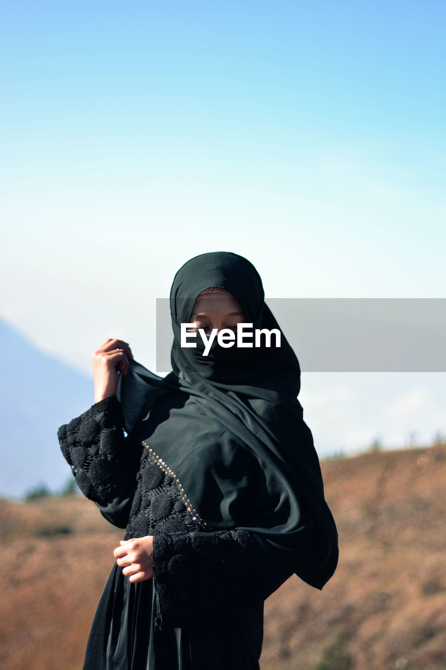 Young woman wearing burka while standing on field against sky