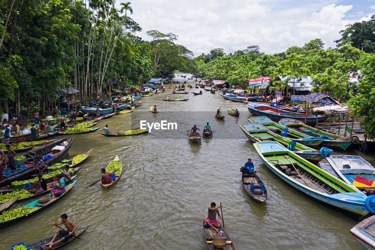 group of people, water, nautical vessel, high angle view, transportation, real people, day, tree, women, men, river, crowd, mode of transportation, nature, large group of people, lifestyles, plant, outdoors, architecture