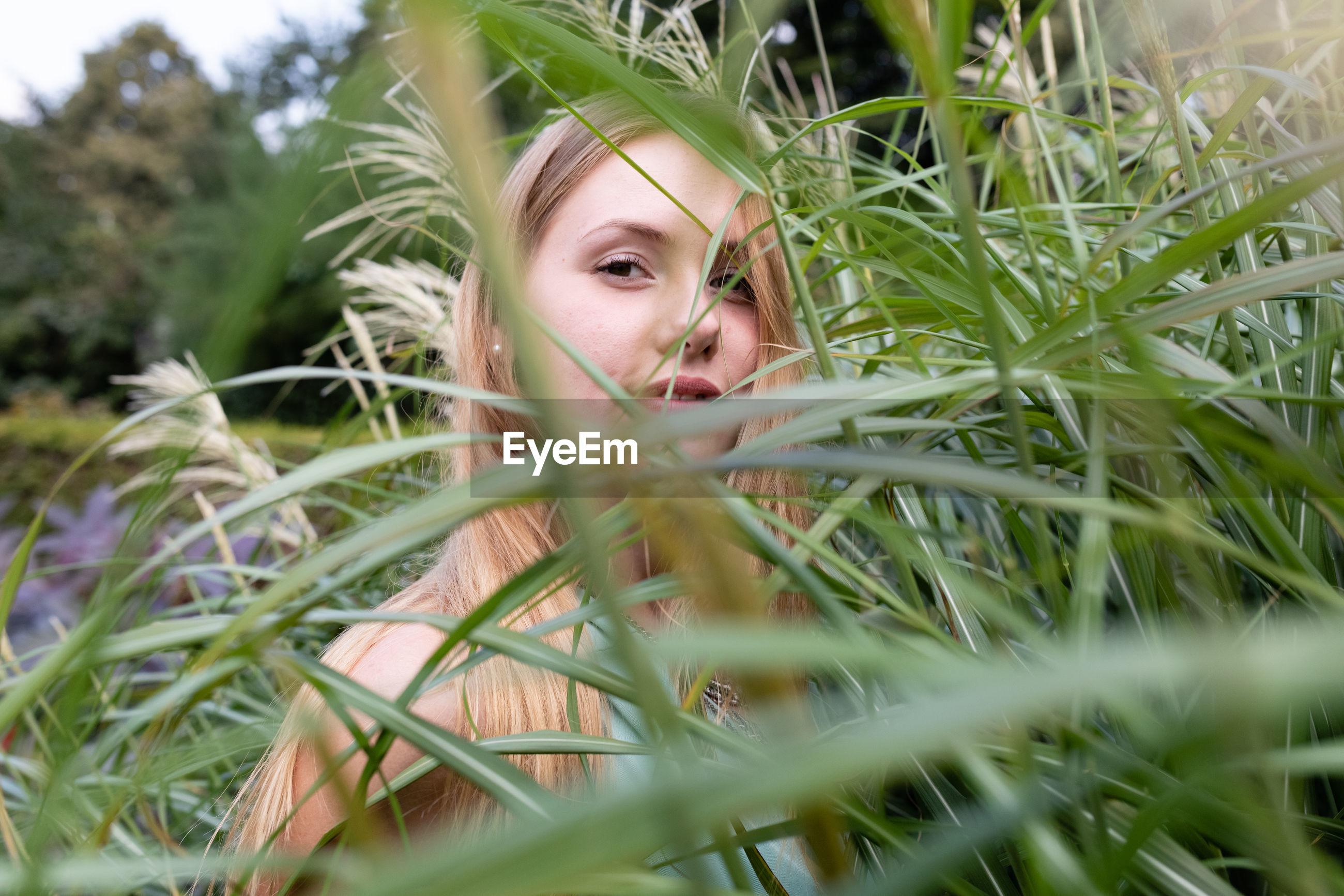 Portrait of woman standing amidst plants