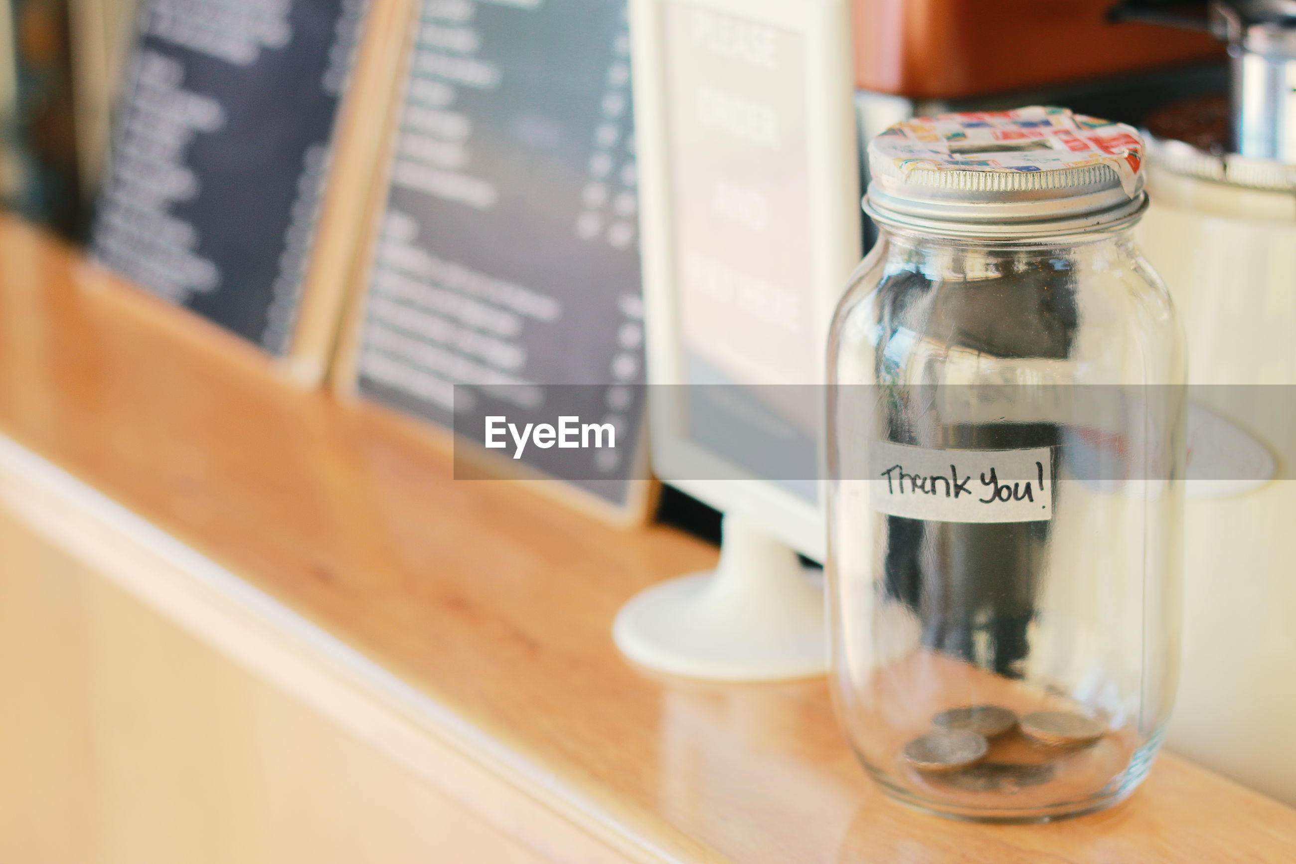 Close-up of coins in glass jar on table at restaurant