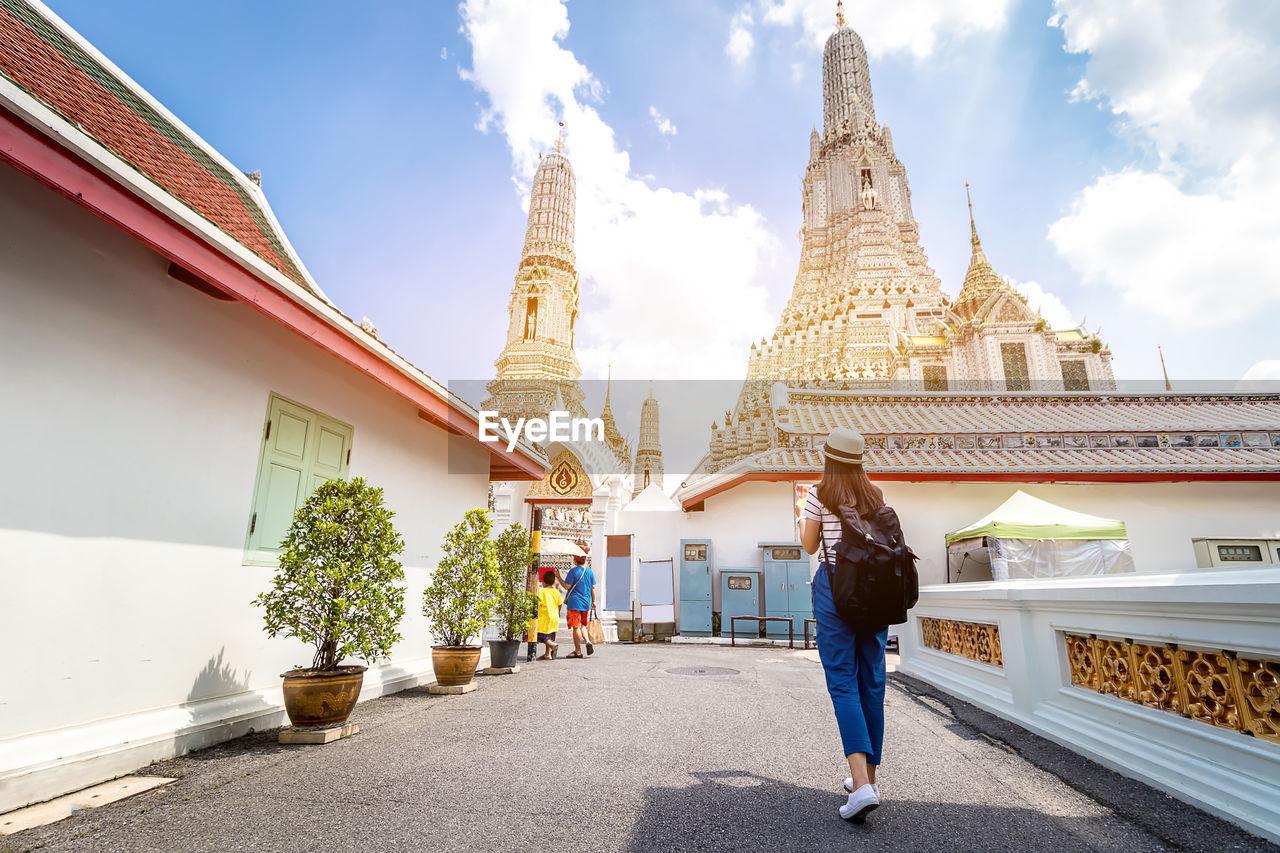 Woman walking against temple