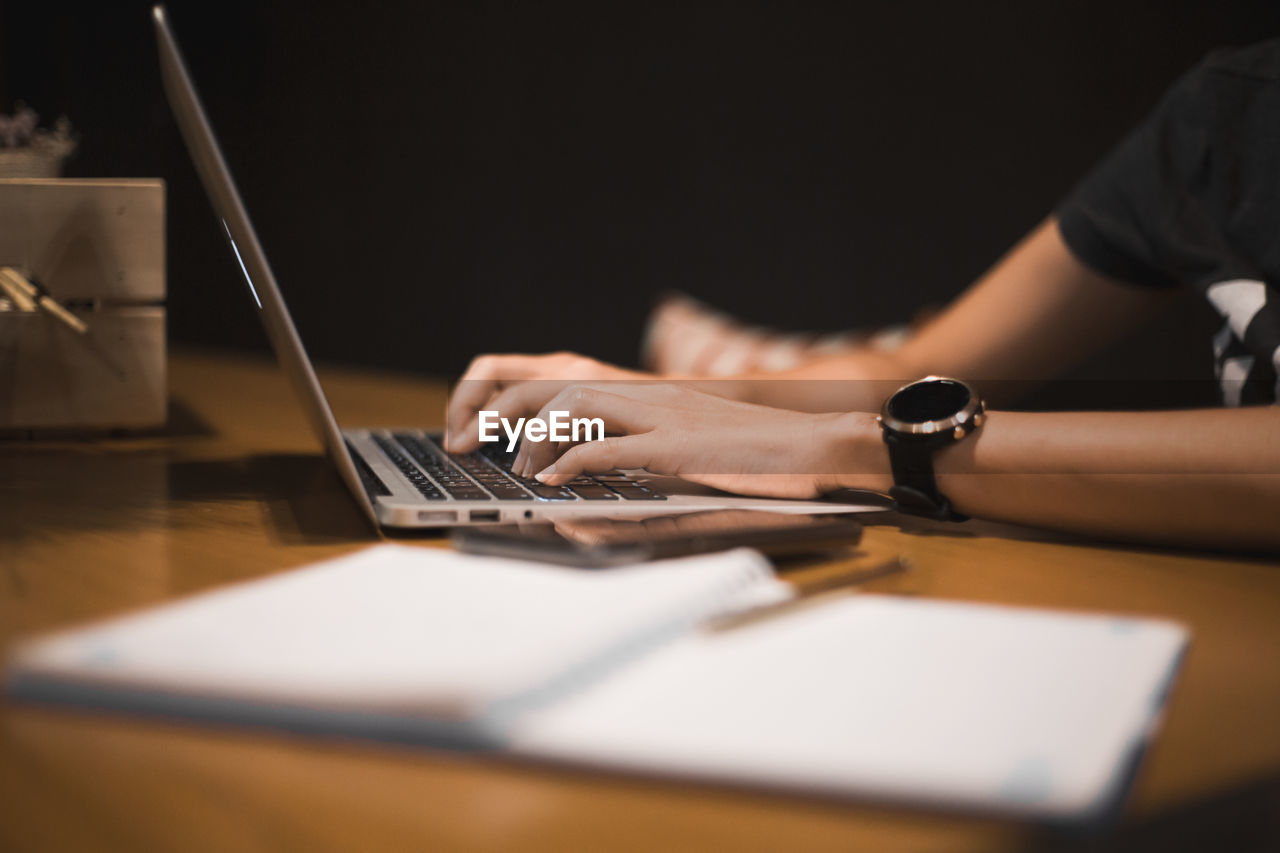 Cropped hands of woman using laptop at table