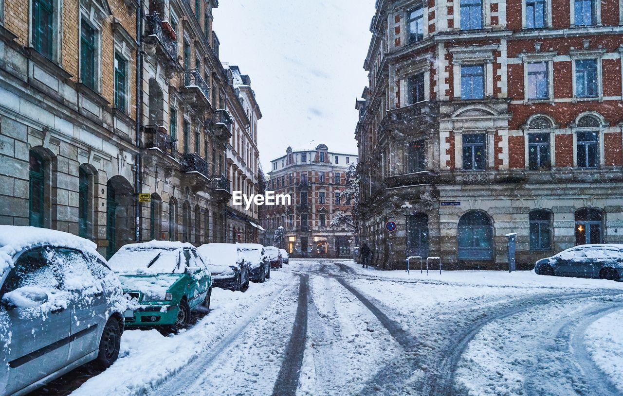 winter, building exterior, cold temperature, architecture, snow, built structure, mode of transportation, transportation, city, motor vehicle, car, land vehicle, building, sky, day, nature, street, road, frozen, no people, outdoors, snowing