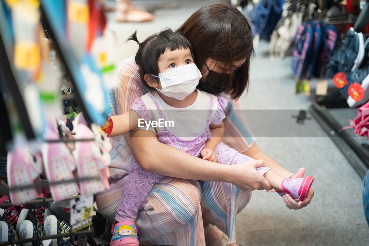 Mother wearing mask putting shoes on of daughter at market