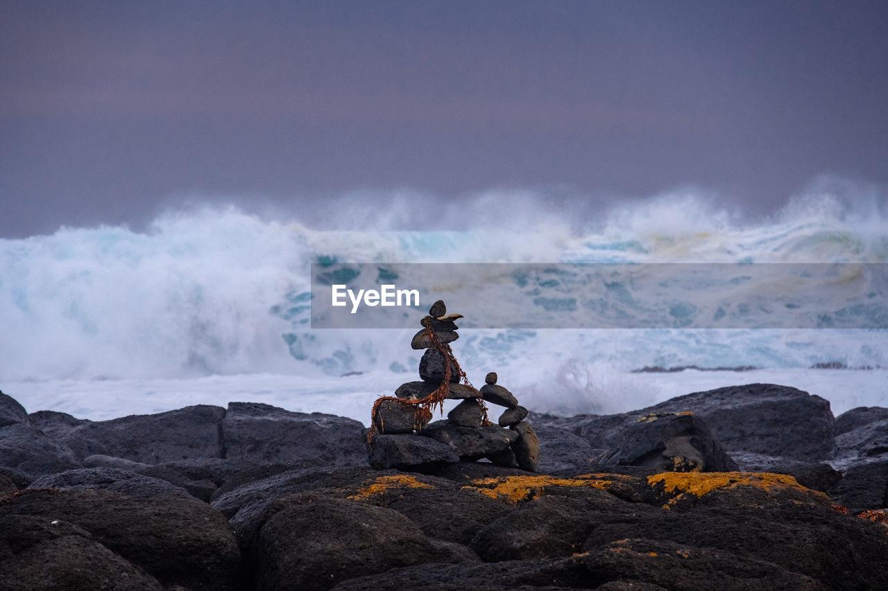 Rocks Arranged On Beach Against Sky