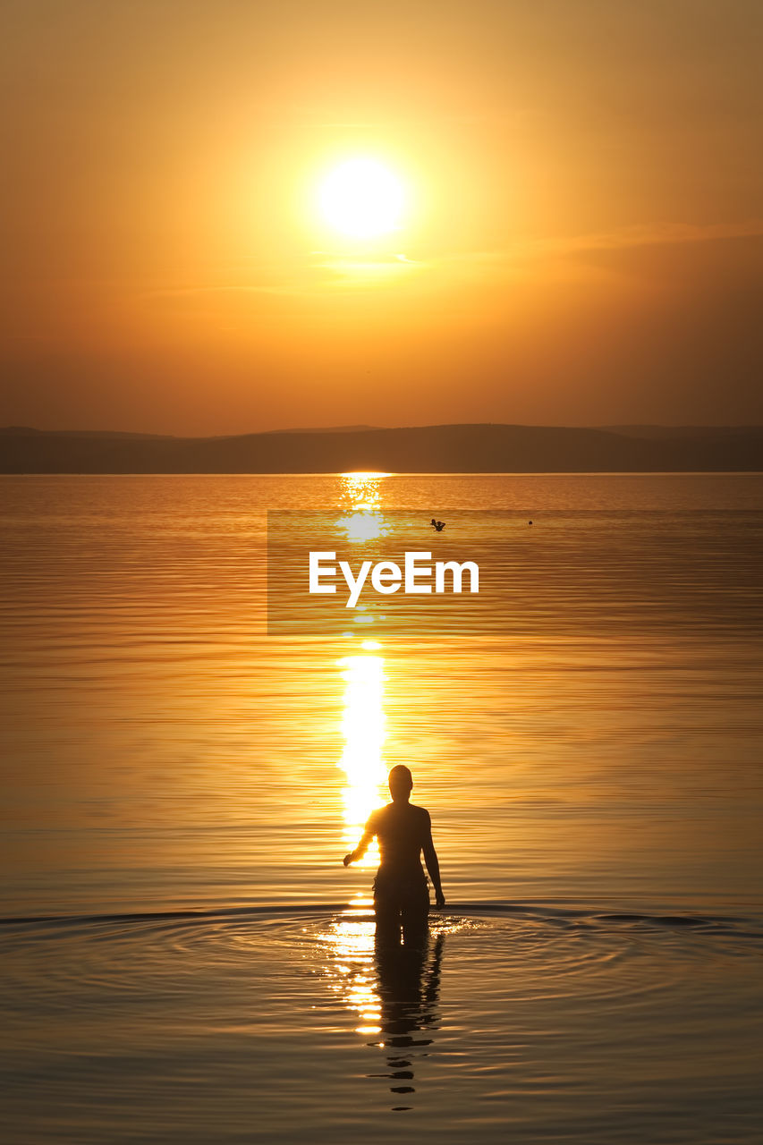 sunset, water, sky, orange color, beauty in nature, silhouette, reflection, real people, scenics - nature, sea, sun, men, lifestyles, one person, nature, sunlight, leisure activity, idyllic, tranquility, outdoors, horizon over water, bright