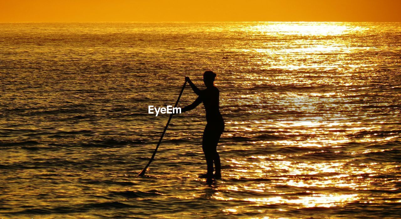 Silhouette Man Paddleboarding In Sea During Sunrise
