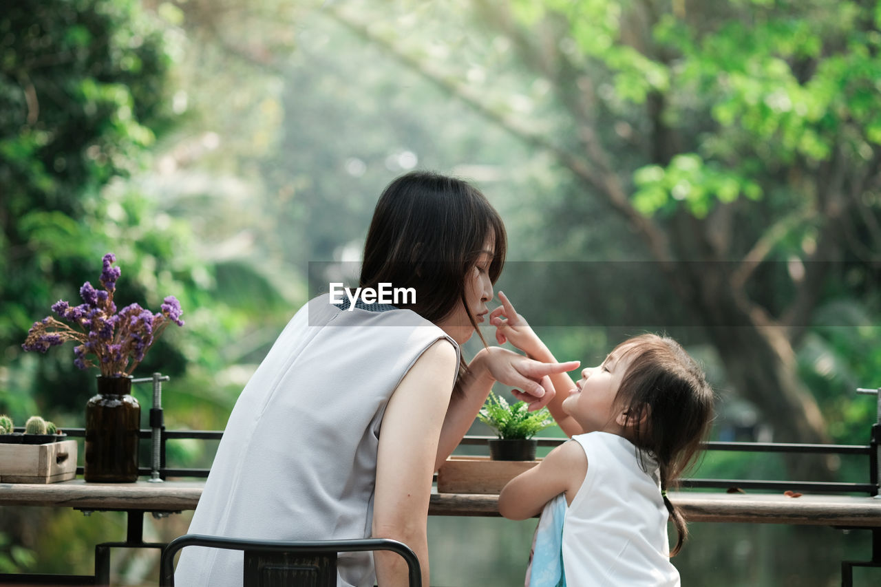 Mother And Daughter Touching Each Other Nose While Sitting At Table