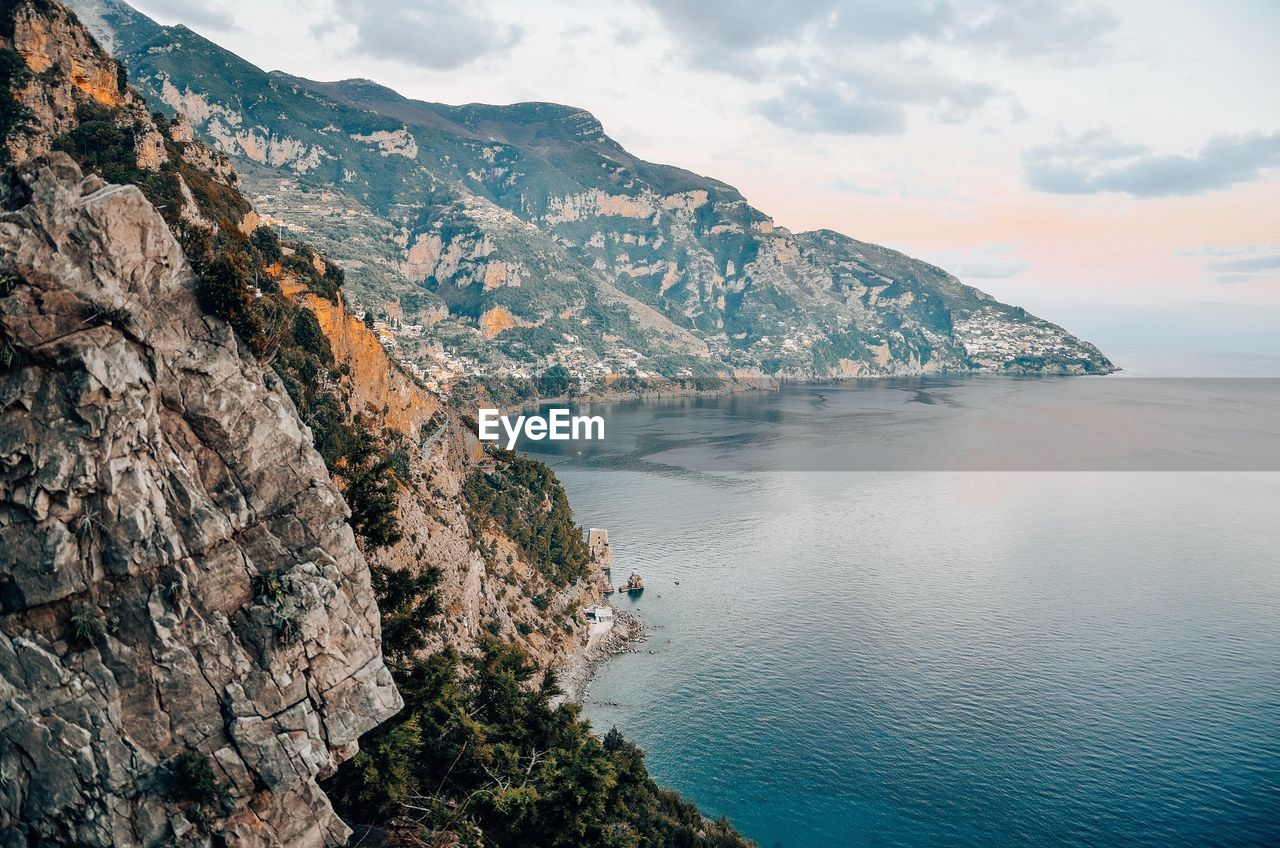 water, beauty in nature, scenics - nature, sea, sky, tranquil scene, tranquility, mountain, cloud - sky, nature, rock, land, no people, rock - object, idyllic, day, cliff, solid, non-urban scene, outdoors, horizon over water, rocky coastline, formation, eroded