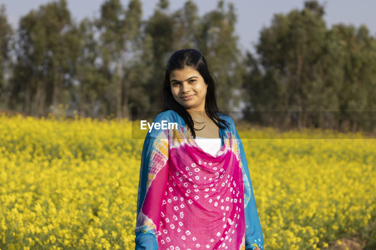 PORTRAIT OF SMILING YOUNG WOMAN STANDING ON YELLOW FLOWER