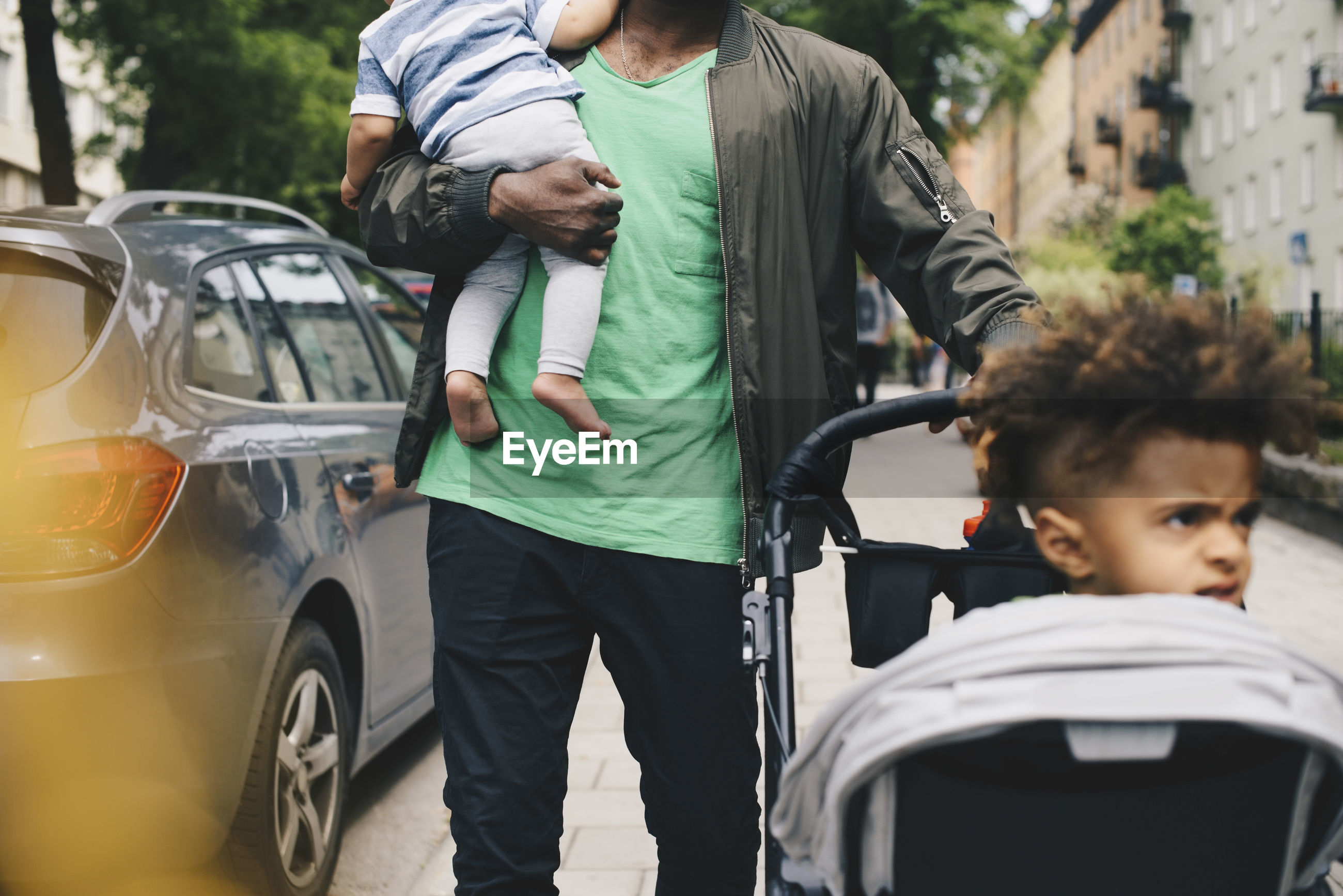 Father walking with children by baby stroller in city
