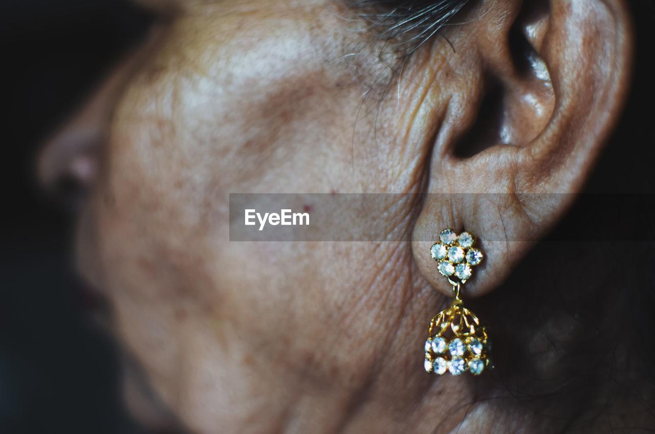 Cropped image of mature woman wearing diamond earring