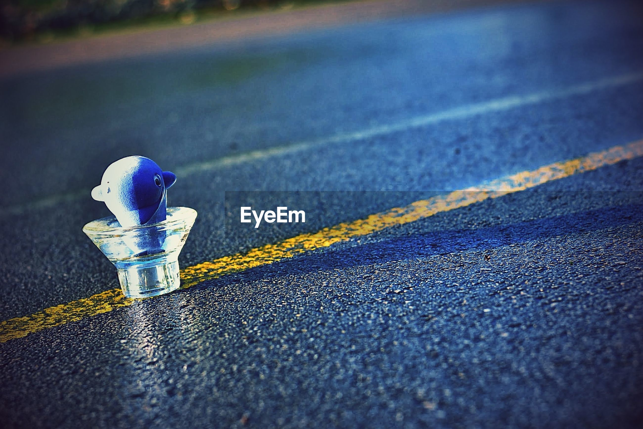 street, road, asphalt, surface level, road marking, selective focus, transportation, close-up, wet, focus on foreground, blue, no people, day, outdoors, yellow, weather, sunlight, guidance, safety, textured