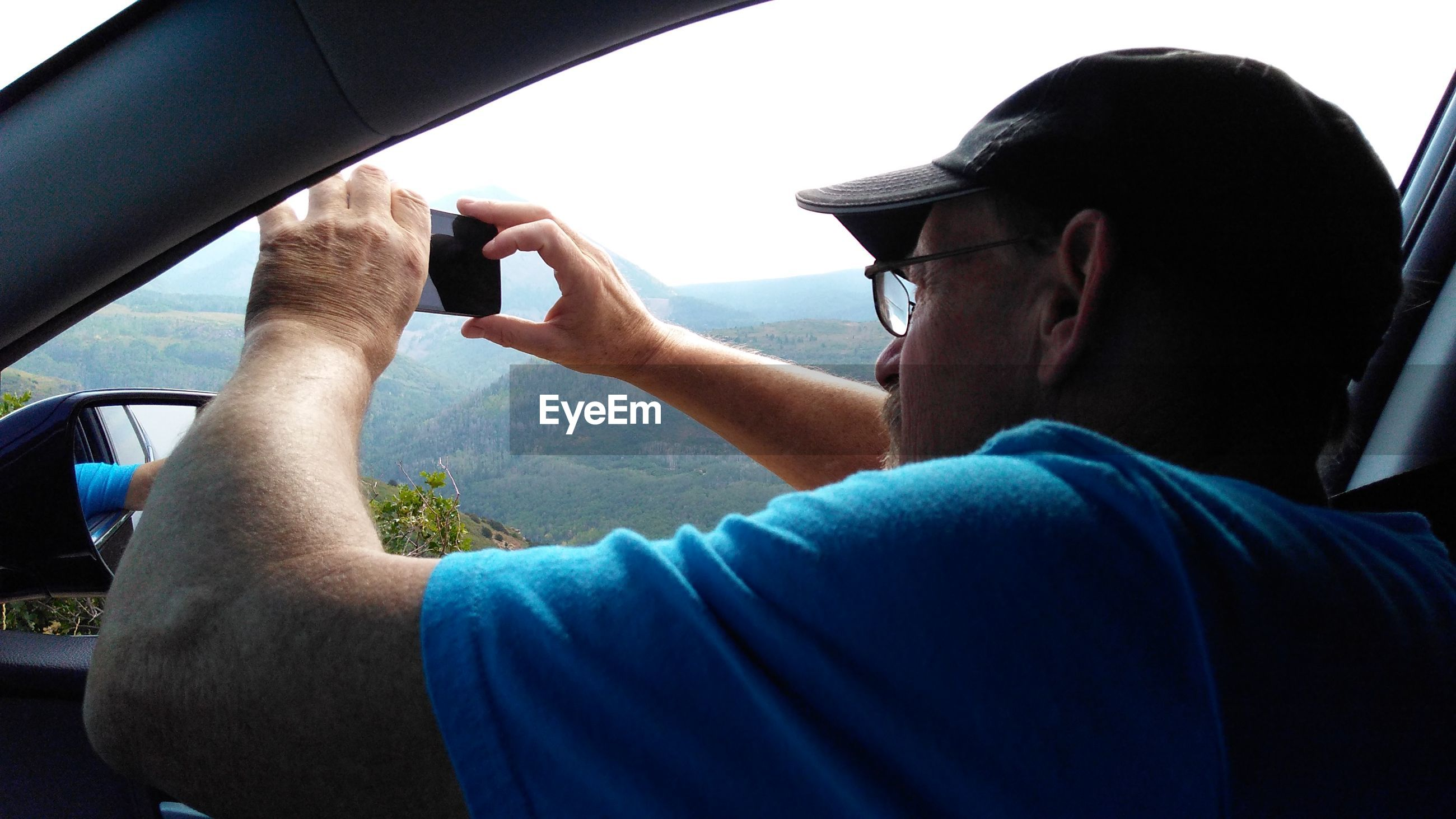 Close-up of man photographing from car window