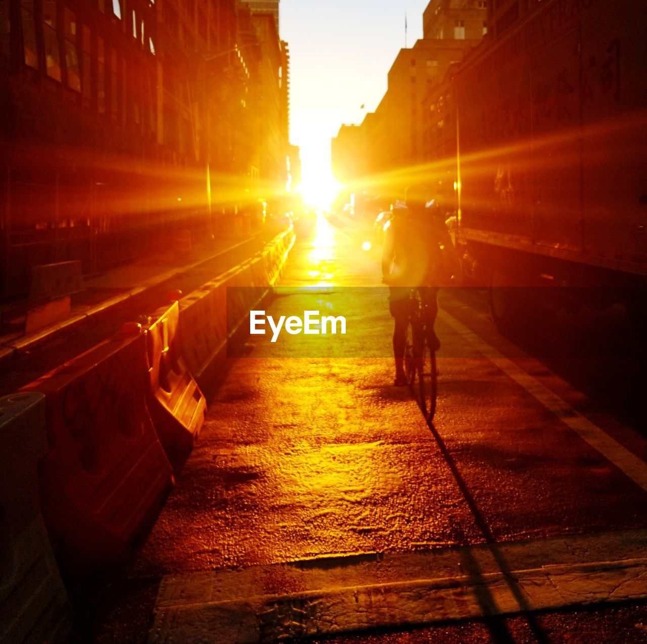 transportation, sunset, mode of transportation, city, sky, real people, sunlight, lens flare, nature, architecture, orange color, street, bicycle, land vehicle, sun, one person, men, built structure, road, outdoors