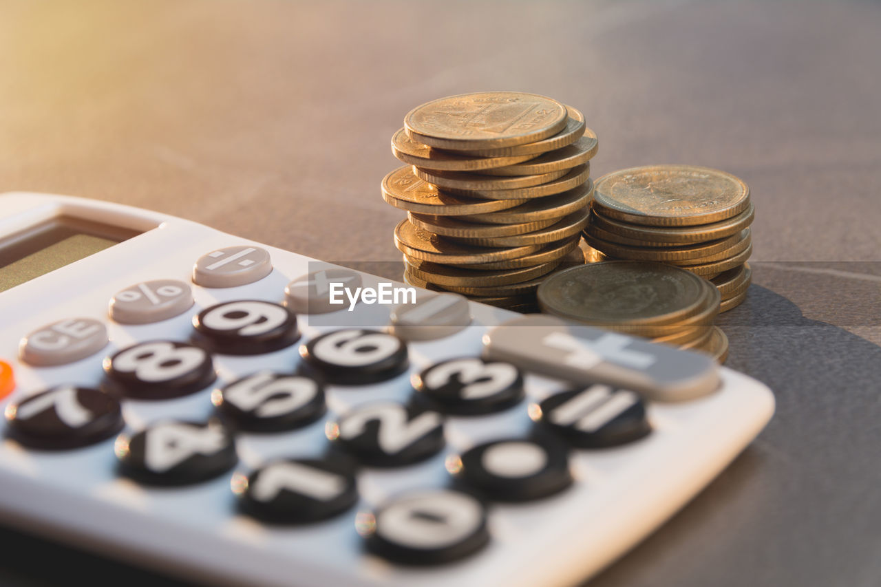 finance, coin, wealth, currency, large group of objects, calculator, business, stack, table, still life, savings, close-up, indoors, no people, investment, arrangement, number, finance and economy, selective focus, metal, economy