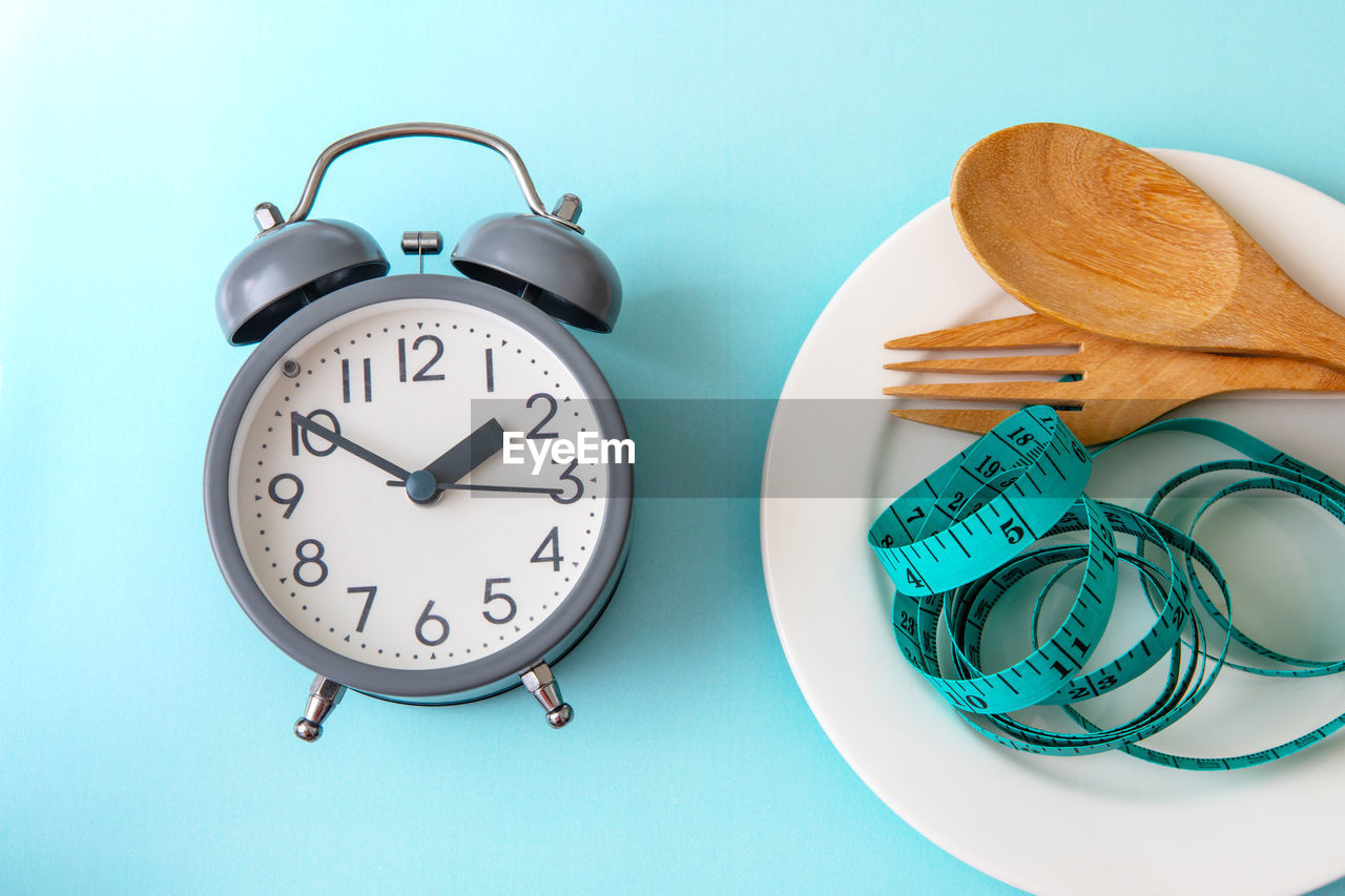 clock, time, still life, indoors, alarm clock, table, close-up, no people, blue, number, pattern, wall - building feature, food and drink, instrument of time, food, wellbeing, high angle view, animal representation, green color, studio shot, turquoise colored, minute hand, blue background