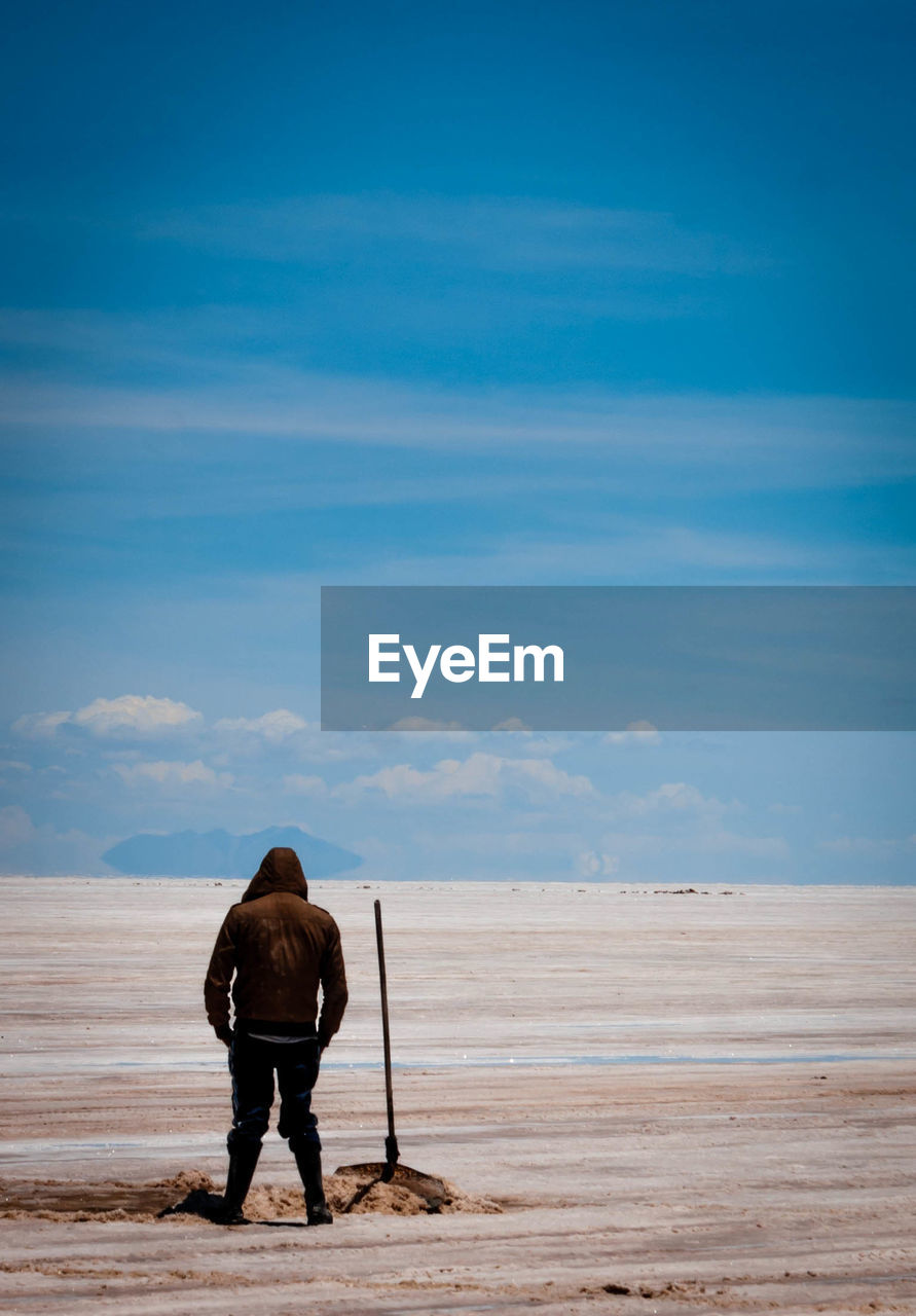 Rear View Of Hooded Person Standing On Salt Flat At Salar De Uyuni Against Sky