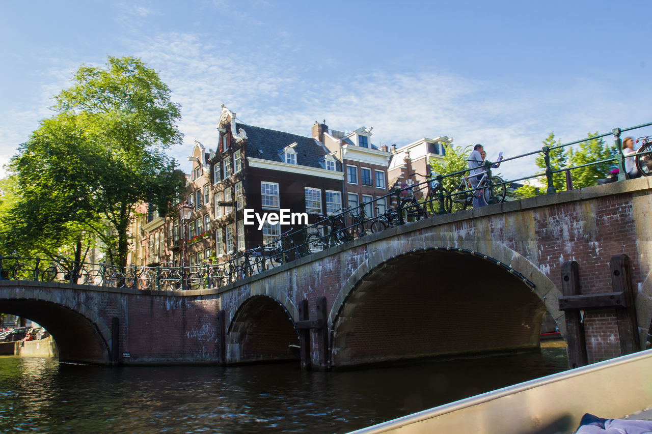 bridge - man made structure, architecture, built structure, connection, tree, river, railing, water, arch, day, outdoors, footbridge, sky, bridge, low angle view, building exterior, no people, city, nature