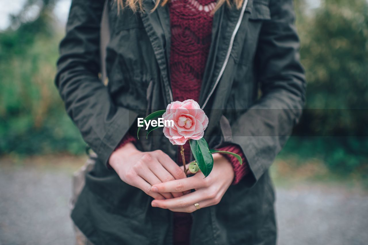 Midsection Of Young Woman Holding Rose Flower