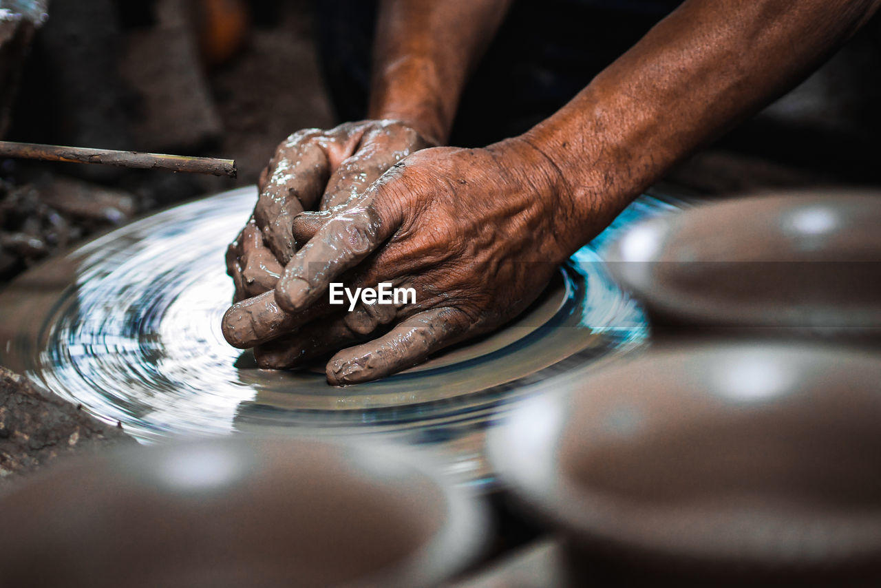 Cropped hands of person working with mud on pottery wheel