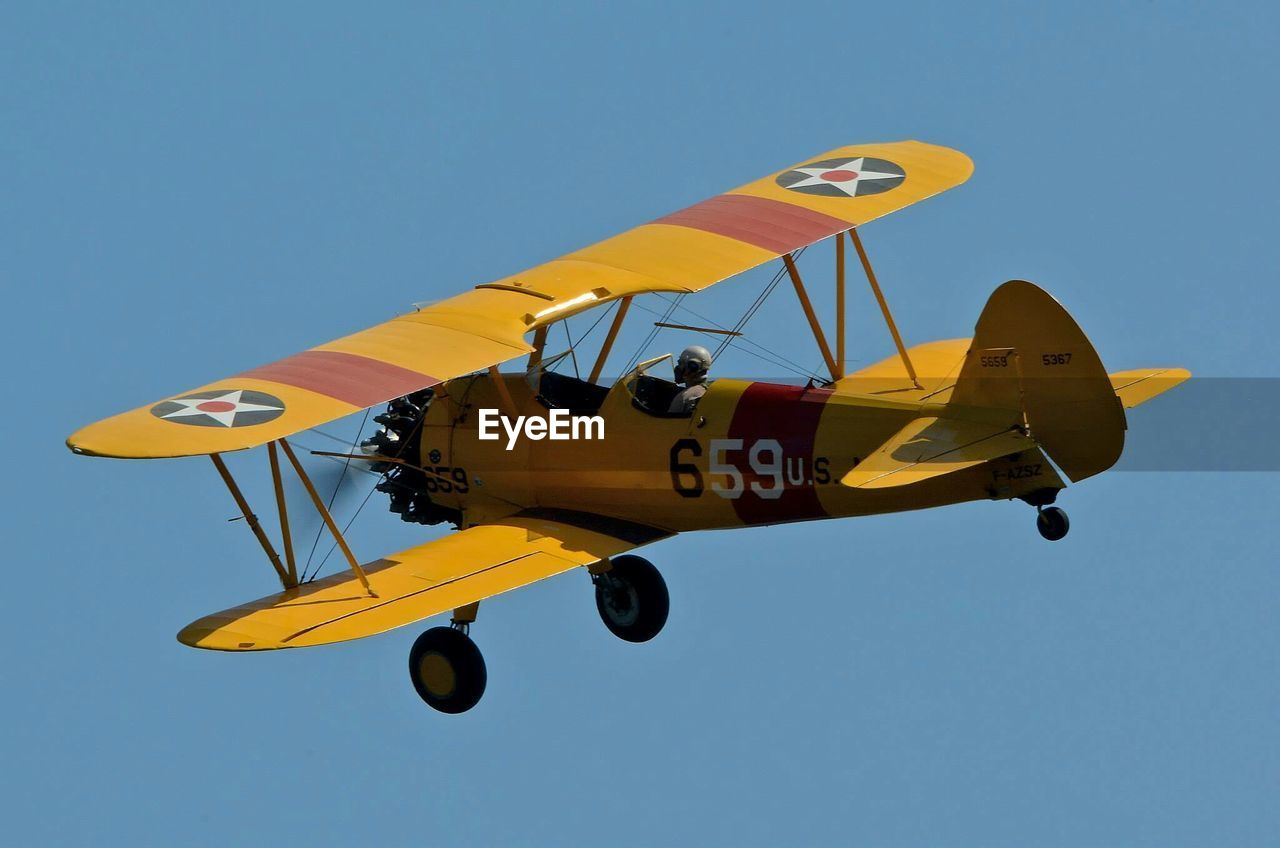 flying, low angle view, transportation, airshow, air vehicle, yellow, leisure activity, clear sky, sky, airplane, mid-air, outdoors, propeller airplane, motion, day, old-fashioned, military airplane, blue, sport, adventure, extreme sports, multi colored, firefighter, aerobatics, people