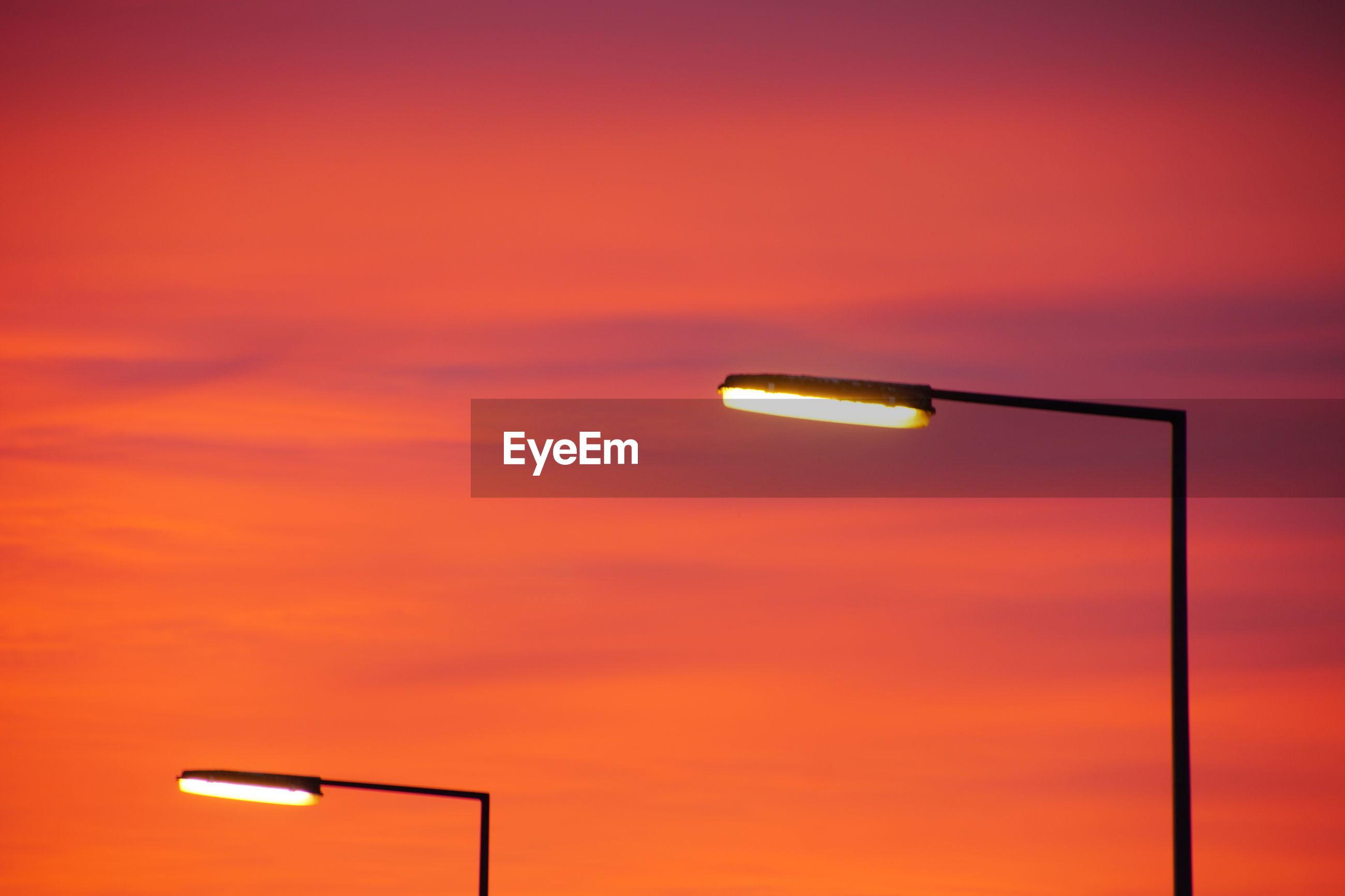 Illuminated street lights against sky during sunset