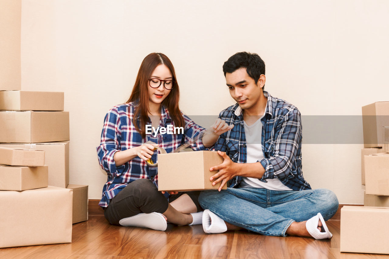 Couple Packing Box While Sitting On Floor