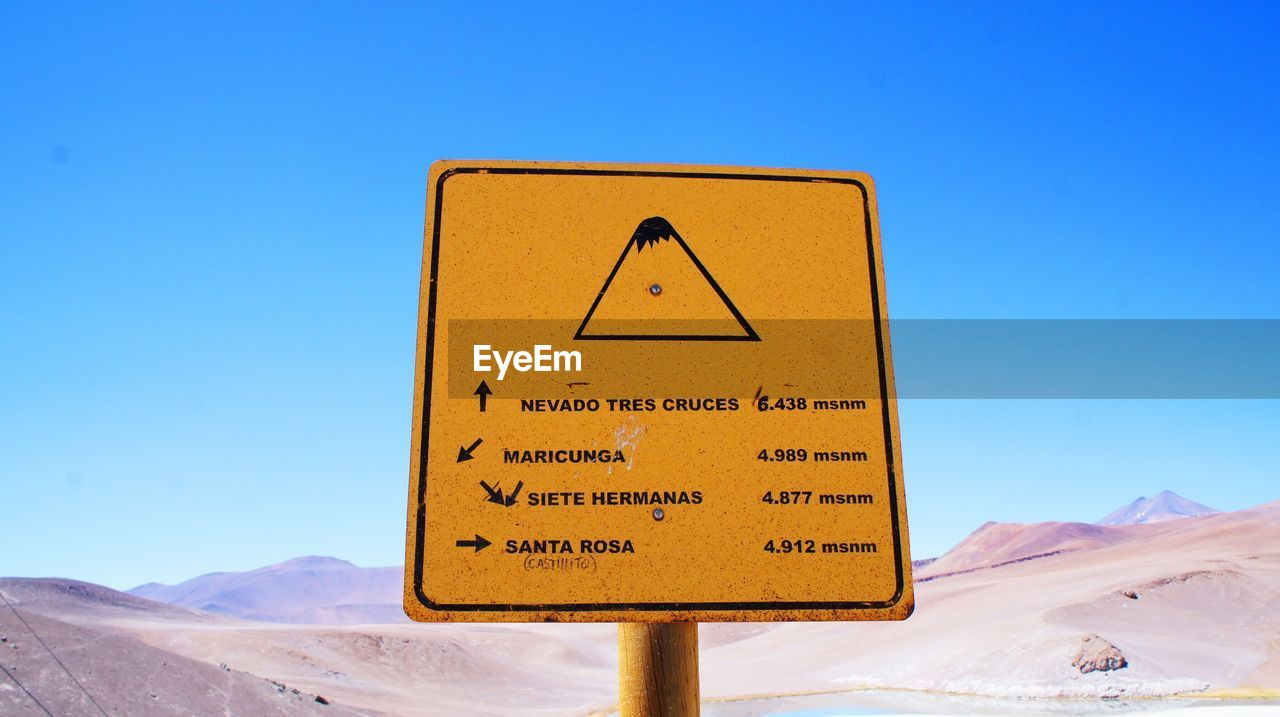 sky, sign, clear sky, communication, snow, cold temperature, blue, winter, nature, warning sign, mountain, text, information, information sign, day, no people, guidance, road sign, scenics - nature