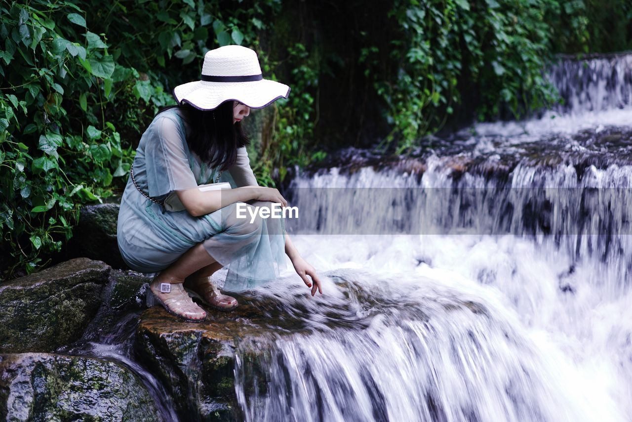 Woman Crouching On Rock At Waterfall In Forest