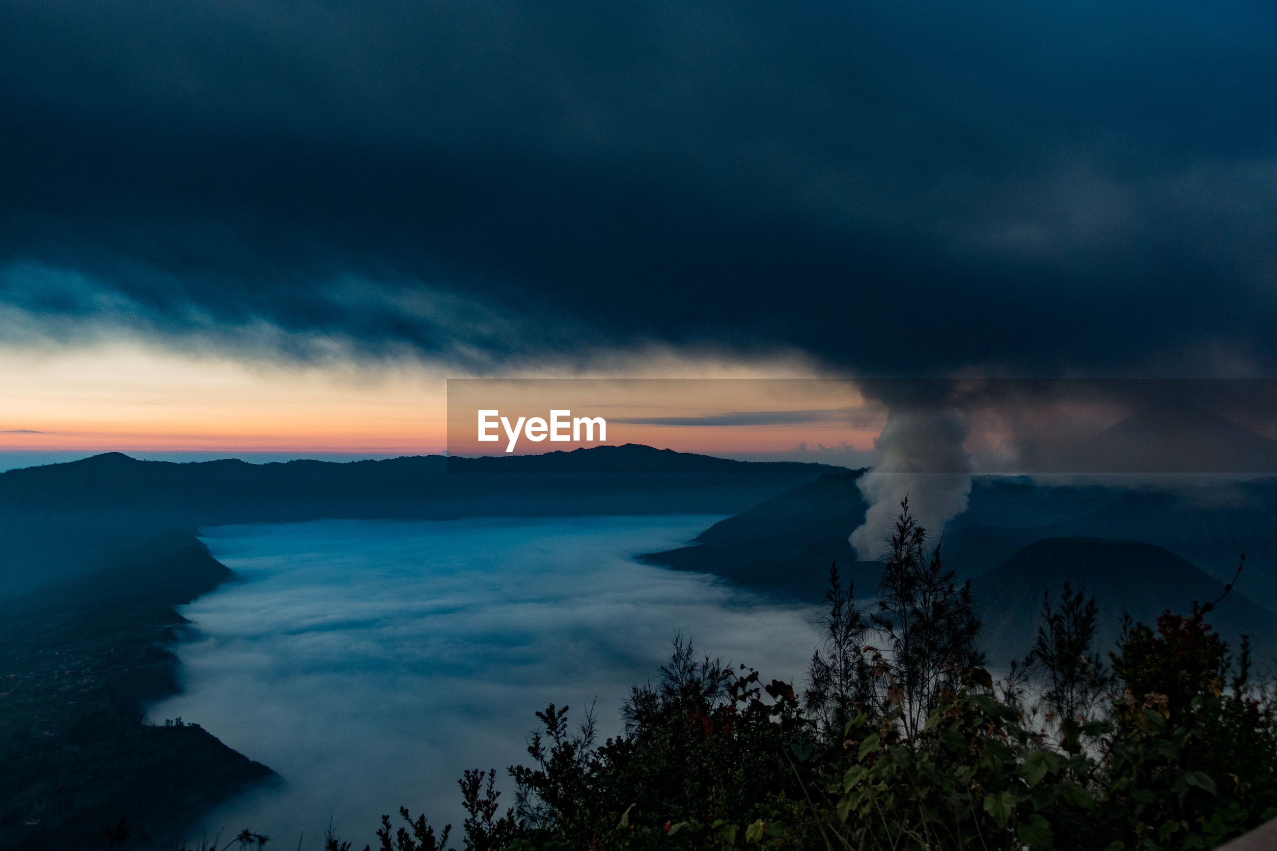 Active volcano at mt bromo against cloudy sky during sunset
