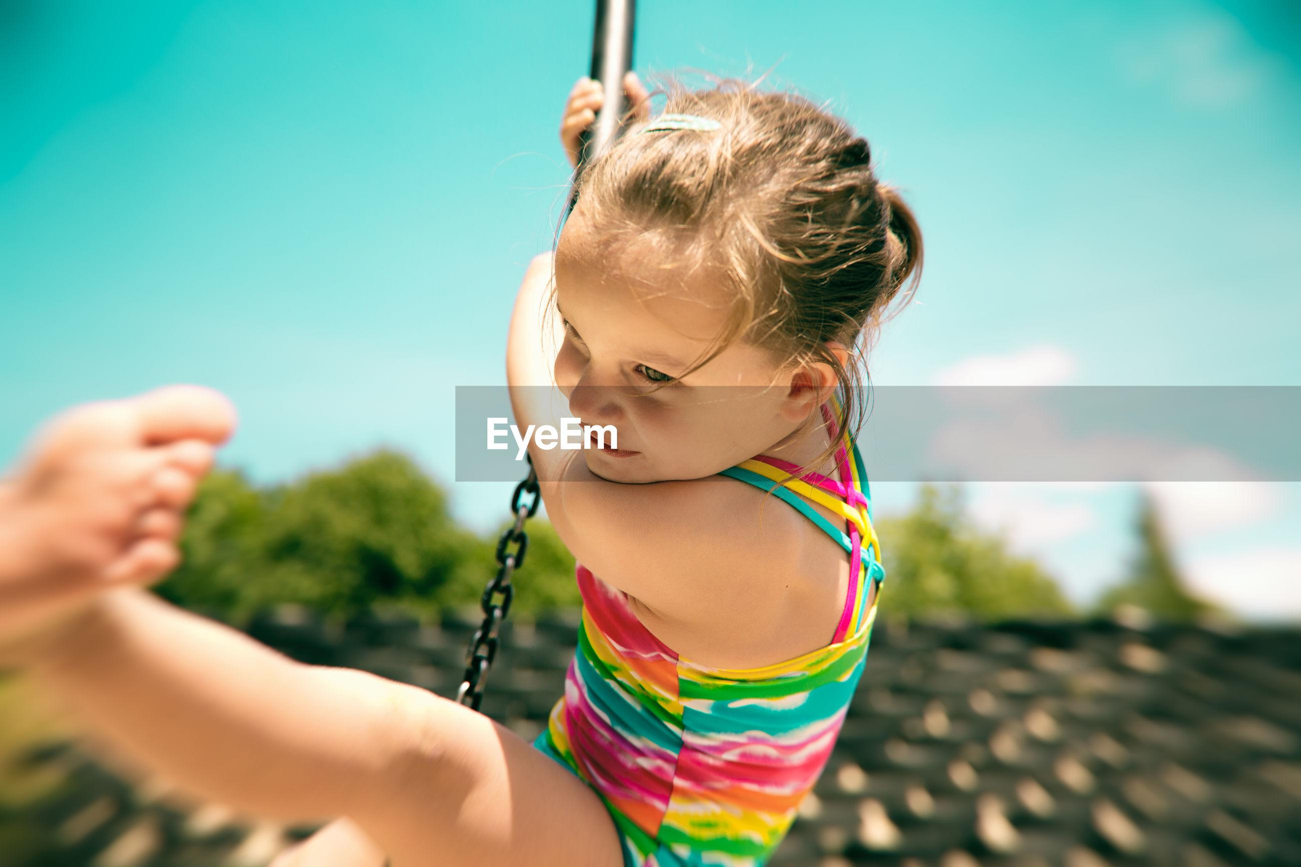 Girl swinging on chain against sky