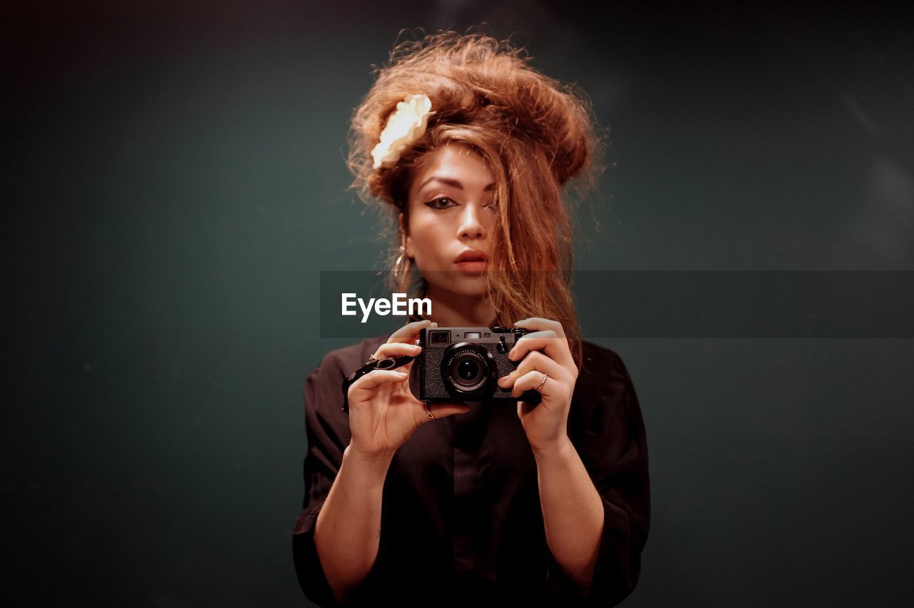 Portrait Of Young Woman With Camera Against Black Background