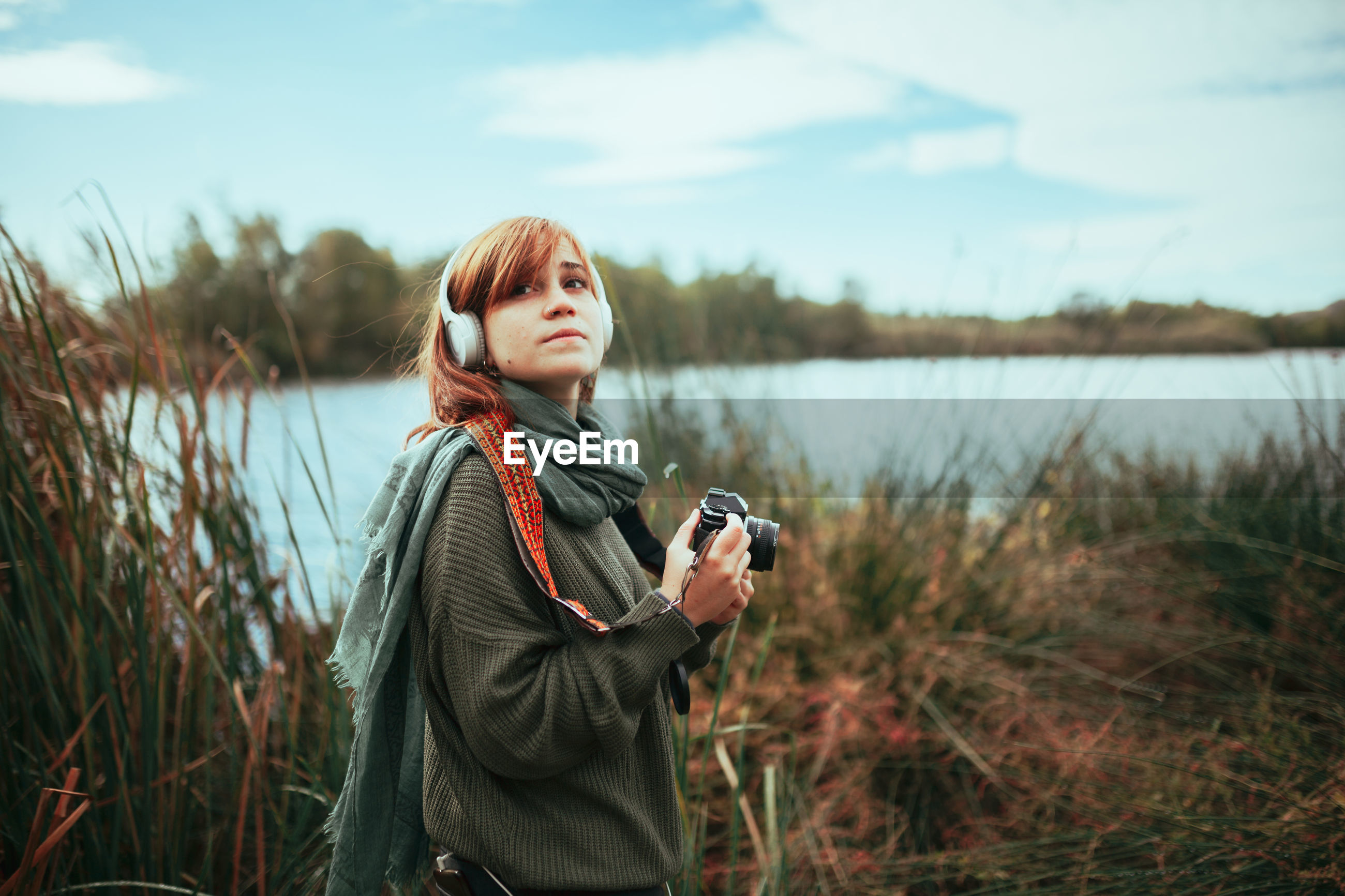 Young woman taking photos near to lake with an old analog camera