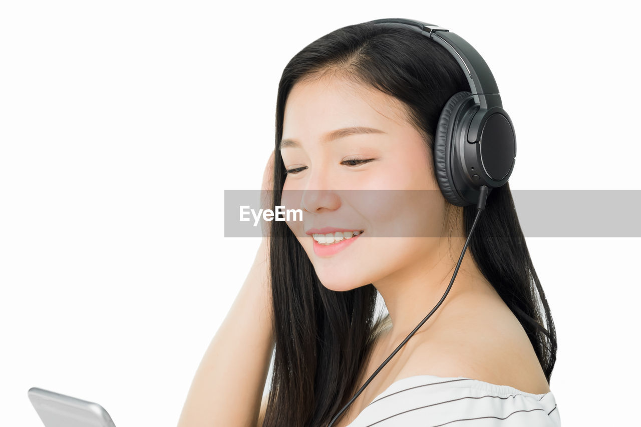 Smiling Woman Listening Music On Headphones Against White Background