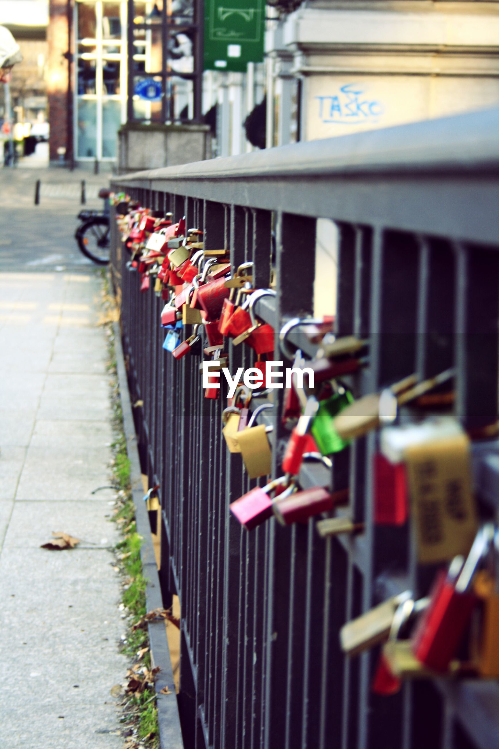 in a row, multi colored, large group of objects, selective focus, focus on foreground, variation, street, padlock, abundance, building exterior, incidental people, day, security, safety, protection, outdoors, lock, built structure, transportation, no people