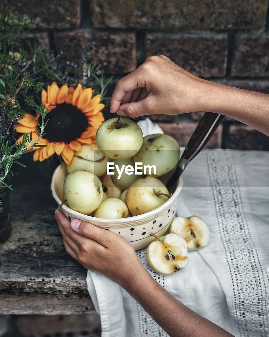 Cropped Hands Of Woman Arranging Apples In Bowl On Table