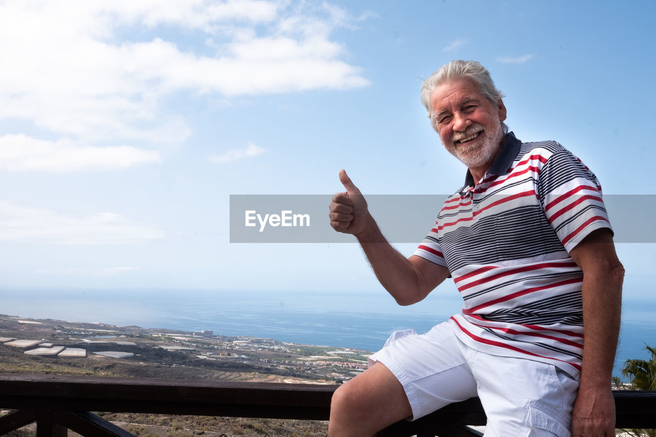 Portrait of smiling senior man showing thumbs up while sitting on railing against sky