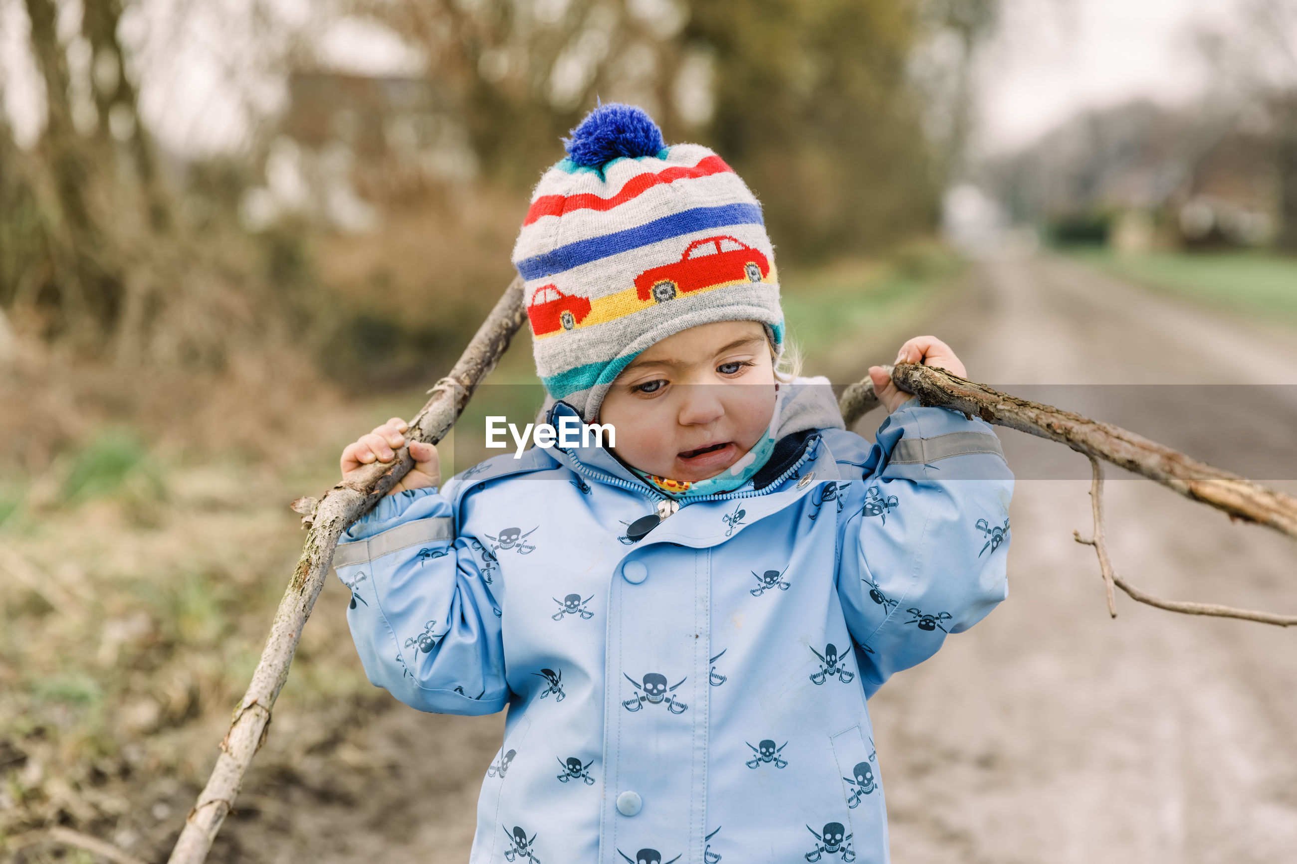 Cute girl wearing warm clothing holding sticks